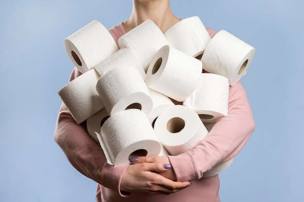 Front view of woman holding too many toilet paper rolls