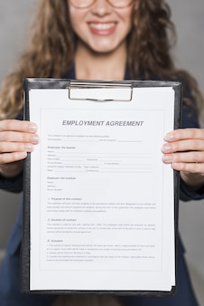 Front view of woman holding up contract for new job