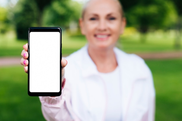 Front view woman holding up a smartphone