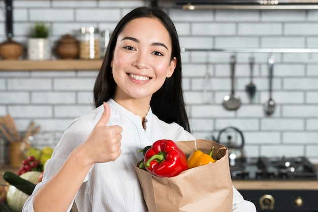Front view of woman holding vegetable bag while showing thumb sign