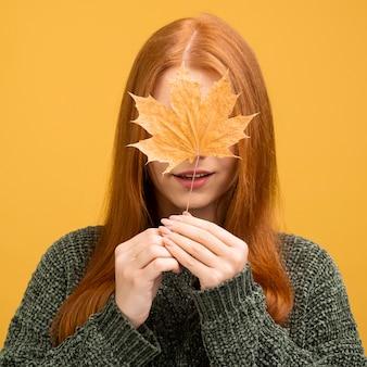 黄色の葉を保持している正面図女性