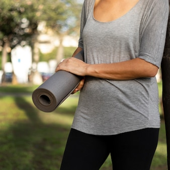 Front view of woman holding yoga mat outdoors