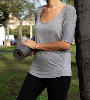Vista frontale della donna che tiene materassino yoga all'esterno