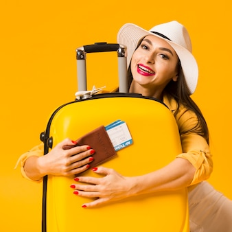 Front view of woman hugging luggage and holding passport with plane tickets