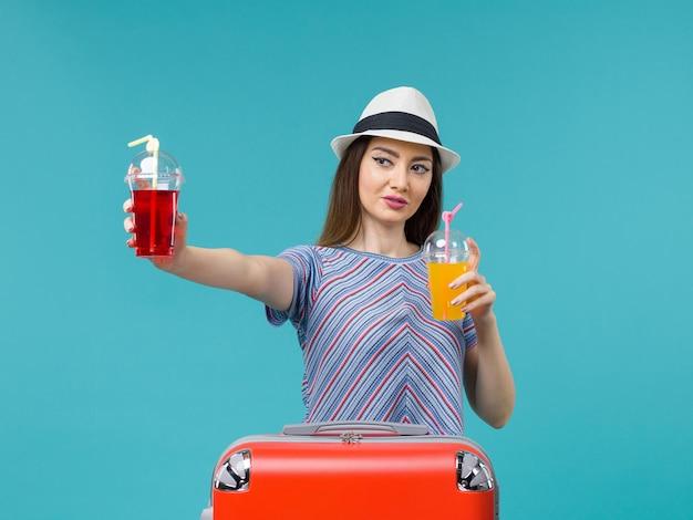 青い背景の水上飛行機の航海の夏の旅で新鮮な飲み物を保持している休暇中の正面図の女性