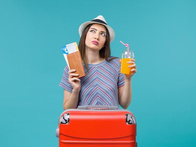 Вид спереди женщина в отпуске, держащая свежий сок и билеты на синем фоне, поездка, путешествие, путешествие, отпуск, море, лето