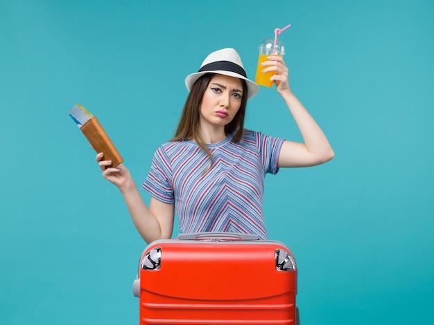 Вид спереди женщина в отпуске, держащая свежий сок и билеты на синем фоне, путешествие, путешествие, отпуск, морское летнее путешествие