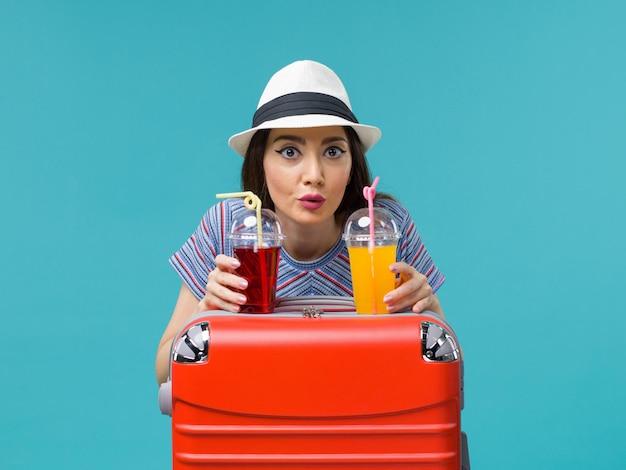 青い背景の水上飛行機の旅の航海の夏にフレッシュジュースを保持している休暇中の正面図の女性