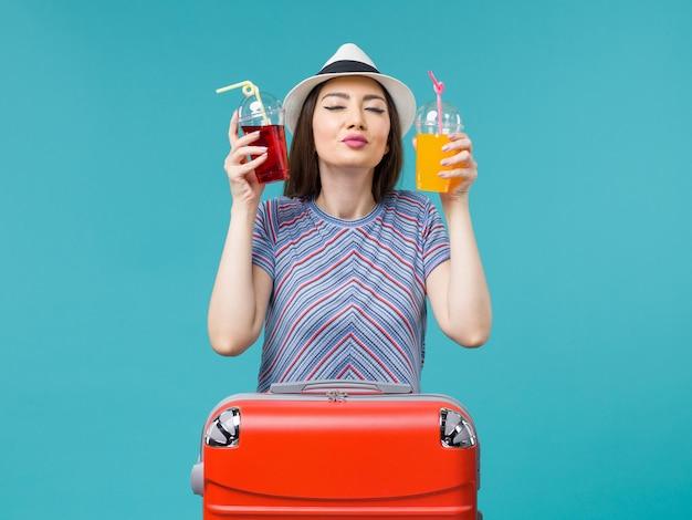 Вид спереди женщина в отпуске, держащая свежие соки на синем фоне, море, летнее путешествие на самолете