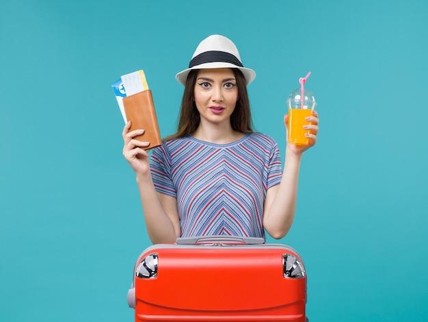 Вид спереди женщина в отпуске, держащая ее сок и билеты на синем фоне, поездка, летнее морское путешествие, путешествие, отпуск