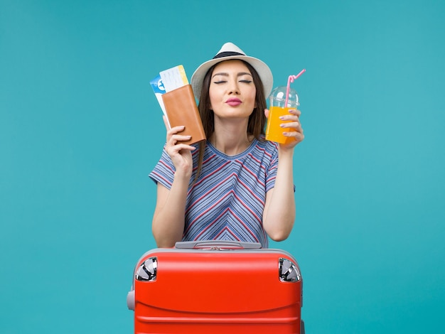 Вид спереди женщина в отпуске, держащая ее сок и билеты на синем письменном столе, летнее путешествие, путешествие, отпуск, море