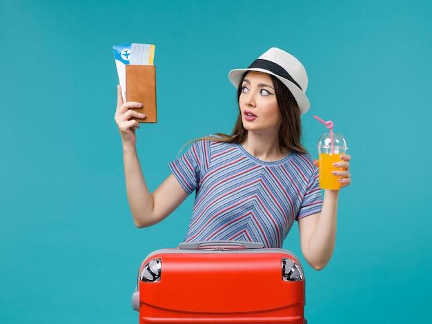 Вид спереди женщина в отпуске, держащая ее сок и билеты на голубом фоне, поездка, летнее морское путешествие, путешествие, отпуск