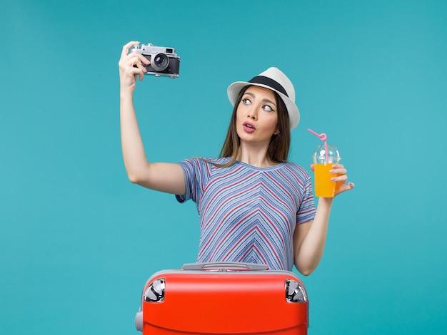 Вид спереди женщина в отпуске, держащая сок и камеру на синем фоне, морское путешествие, летнее путешествие, путешествие, отпуск