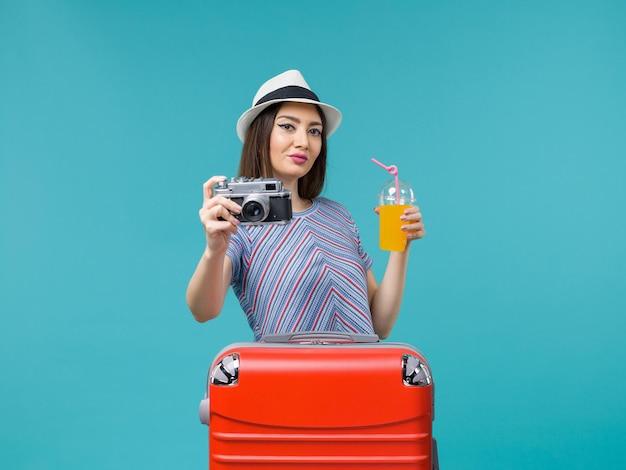 Вид спереди женщина в отпуске, держащая сок и камеру на синем фоне, путешествие, летнее путешествие, путешествие, отпуск, море