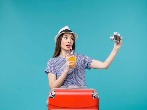 Вид спереди женщина в отпуске, держащая сок и камеру на синем фоне, путешествие, летнее путешествие, отпуск, морское путешествие