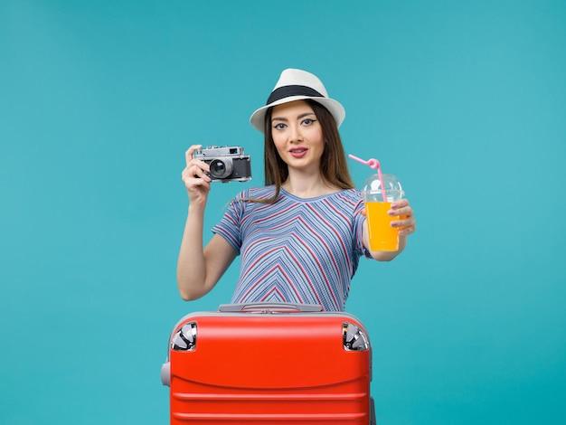 Вид спереди женщина в отпуске, держащая сок и камеру на голубом фоне, путешествие, летнее путешествие, путешествие, отпуск, море