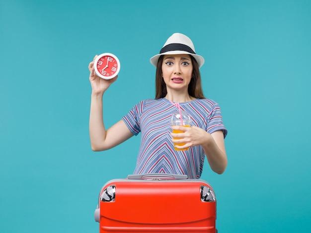 Вид спереди женщина в отпуске, держащая сок и часы на синем фоне, путешествие, отпуск, морское путешествие, путешествие