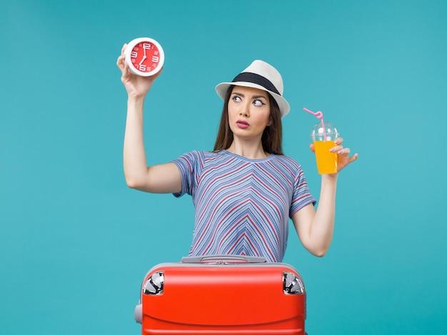 Вид спереди женщина в отпуске, держащая сок и часы на синем столе, путешествие, отпуск, морское путешествие