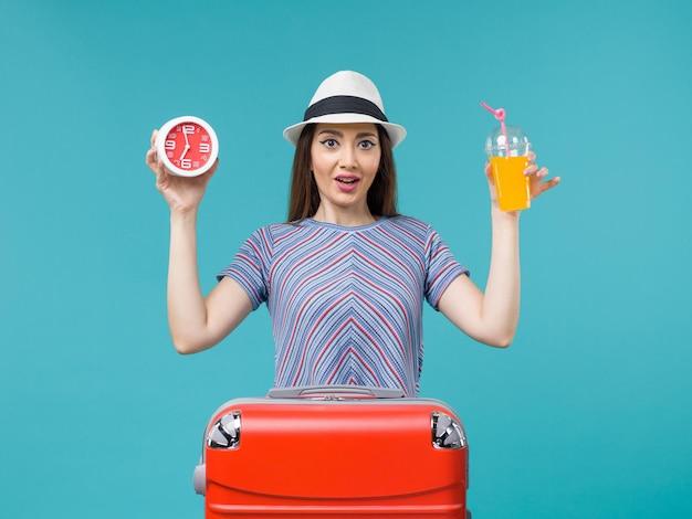 Вид спереди женщина в отпуске, держащая сок и часы на голубом фоне, путешествие, отпуск, морское путешествие, путешествие