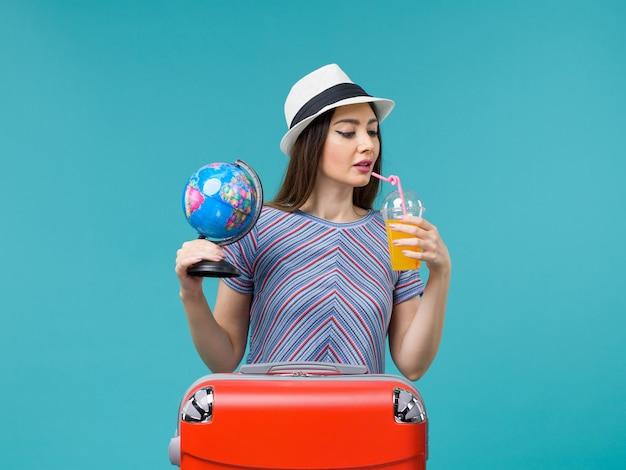 Вид спереди женщина в отпуске, держащая сок и глобус на синем фоне, морское путешествие, отпуск, летнее путешествие, путешествие