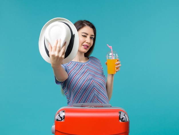 Вид спереди женщина в отпуске, держащая сок и шляпу на синем фоне, путешествие, отпуск, морское путешествие, путешествие