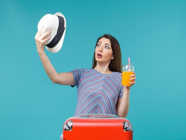 Вид спереди женщина в отпуске, держащая сок и шляпу на синем фоне, путешествие, путешествие, отпуск, морское путешествие