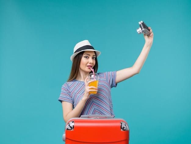 Вид спереди женщина в отпуске, держащая сок и делающая фото с камерой на синем фоне, путешествие, летнее путешествие, отпуск, морское путешествие