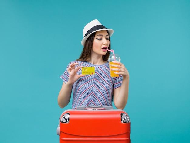 Вид спереди женщина в отпуске, держащая сок и желтую банковскую карту на синем дне, морское путешествие, отпуск, летнее путешествие