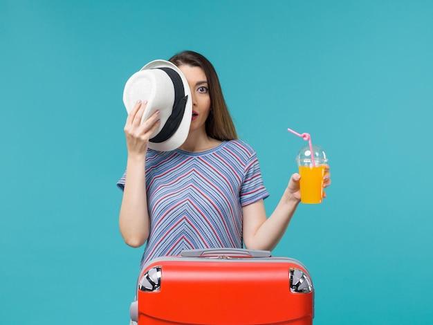 Вид спереди женщина в отпуске, держащая сок на синем фоне, путешествие, путешествие, отпуск, морское путешествие