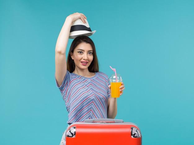 Вид спереди женщина в отпуске, держащая сок на синем фоне, путешествие, летнее путешествие, отпуск, морское путешествие