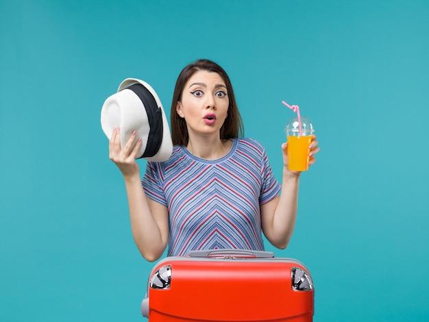 Вид спереди женщина в отпуске, держащая сок на голубом фоне, путешествие, путешествие, отпуск, морское путешествие