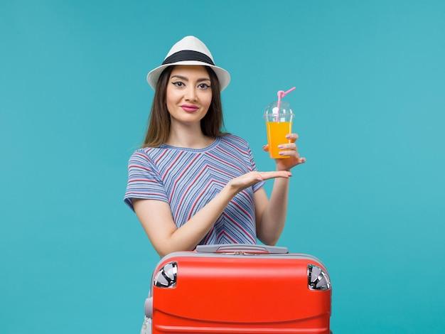 파란색 배경 여행 항해 휴가 여성 여행에 그녀의 주스를 들고 그녀의 빨간 가방과 함께 휴가에 전면보기 여자