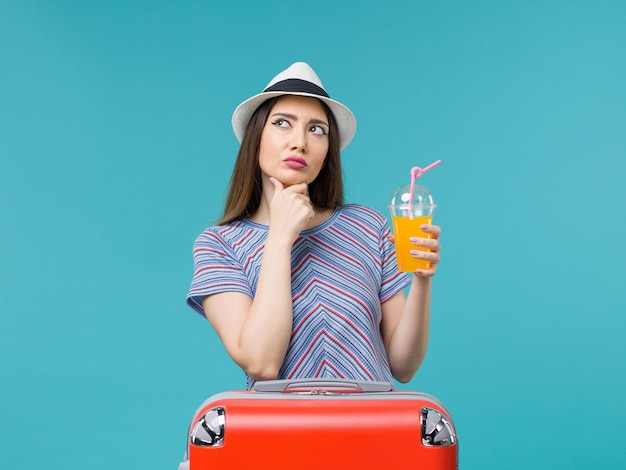 파란색 배경 여행 여행 항해 휴가 여성에 그녀의 주스를 들고 그녀의 빨간 가방과 함께 휴가에 전면보기 여자