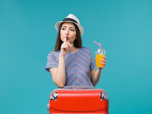 밝은 파란색 배경 여행 여행 항해 휴가 여성에 그녀의 주스를 들고 그녀의 빨간 가방과 함께 휴가에 전면보기 여자