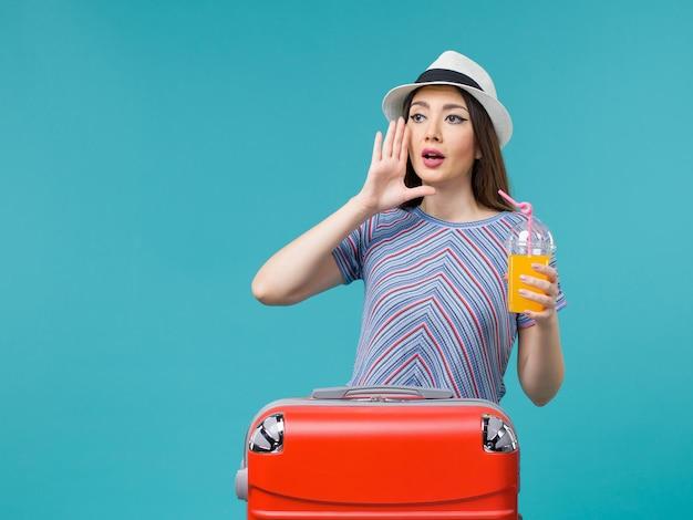 青い背景の旅の旅の航海の休暇の女性の女性に彼女のジュースを保持している彼女の赤いバッグと休暇中の正面図の女性