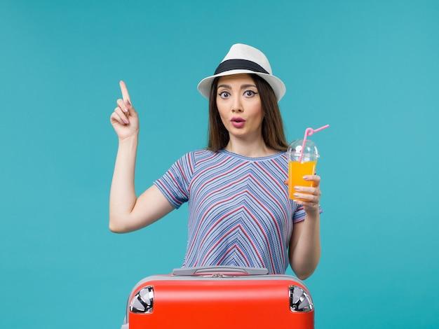 밝은 파란색 배경 여행 항해 휴가 여성 여행에 그녀의 주스를 들고 그녀의 빨간 가방과 함께 휴가에 전면보기 여자