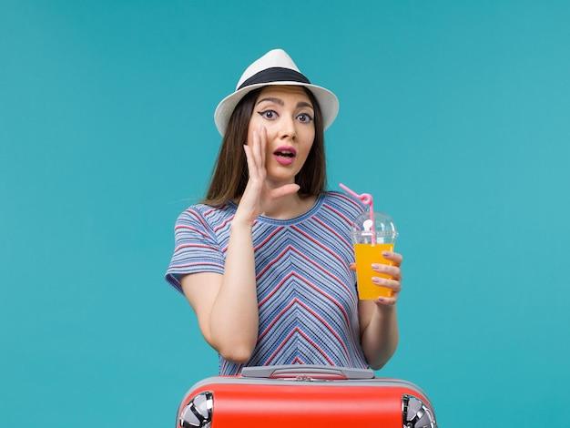 水色の背景に彼女のジュースを保持している彼女の赤いバッグと休暇中の正面図の女性旅行旅行航海休暇の女性