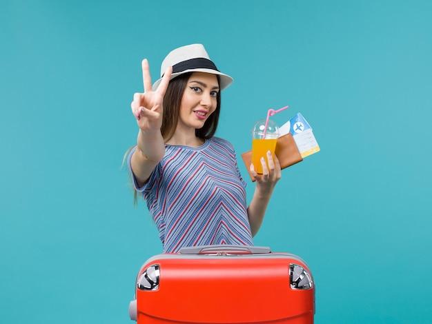 밝은 파란색 배경 여행 여행 항해 휴가 여성에 티켓과 주스를 들고 그녀의 빨간 가방 휴가에 전면보기 여자