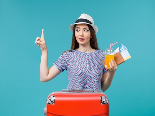 파란색 배경 여행 여행 항해 휴가 여성에 티켓과 주스를 들고 그녀의 빨간 가방과 함께 휴가에 전면보기 여자