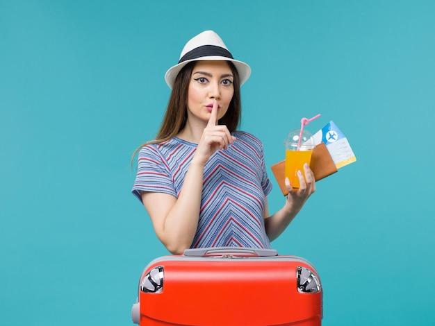 水色の背景の旅旅行航海休暇の女性にチケットとジュースを保持している彼女の赤いバッグと休暇中の正面図の女性