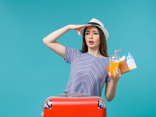 水色の背景の旅の航海休暇の女性の旅行でチケットとジュースを保持している彼女の赤いバッグと休暇中の正面図の女性