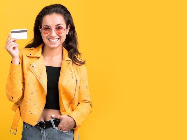 彼女のショッピングカードを示す黄色いジャケットの正面図の女性