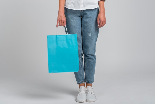 Front view of woman in jeans holding shopping bag