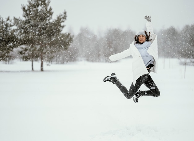Front view of woman jumping in the air outdoors in winter