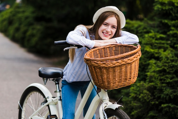 Front view woman leaning against bike handlebar