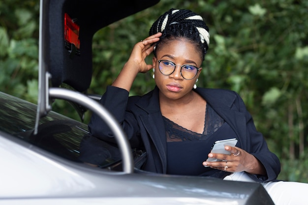 Front view of woman leaning into her car's trunk while holding smartphone
