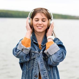 Женщина вид спереди слушает музыку на берегу моря