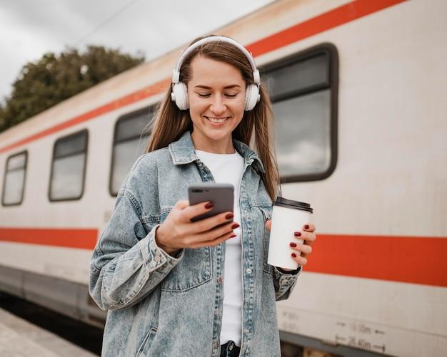 駅で音楽を聴いている正面図の女性
