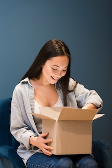 Front view of woman looking in box after ordering online