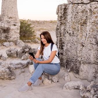 Donna di vista frontale che osserva sul suo telefono mentre era seduto su una roccia